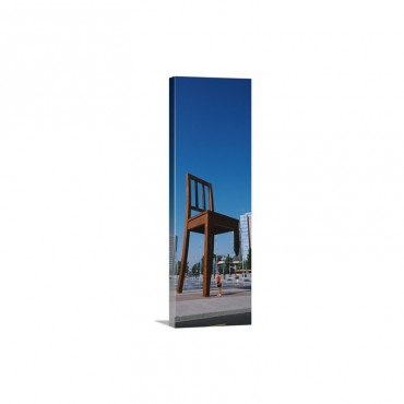 Woman Standing Under A Sculpture Of Large Broken Chair Geneva Switzerland Wall Art - Canvas - Gallery Wrap